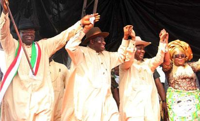 President Goodluck Jonathan flanked by Vice President Namadi Sambo and the Bayelsa State PDP Gubernatorial Candidate, Mr. Seriake Henry Dickson (l) while the First Lady, Dame Patience Jonathan also grabs the hands of the wife of the candidate, Mrs. Seriake Dickson as they danced round the arena during the grand finale of the PDP Governorship Campaign at the Samson Siasia Stadium, Yenagoa, Bayelsa State. Photo by Abayomi Adeshida