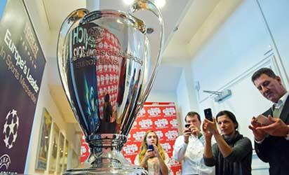 Employees of a radio station take photographs of the UEFA Champions League trophy in the southern German city of Munich on May 14, 2012 as  FC Bayern Munich face Chelsea in the final today in Munich. AFP PHOTO