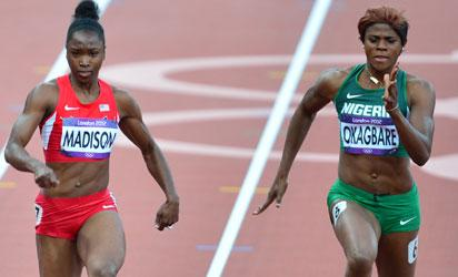 US' Tianna Madison (L) and Nigeria's Blessing Okagbare compete in the women's 100m heats at the athletics event during the London 2012 Olympic Games on August 3, 2012 in London.  AFP PHOTO