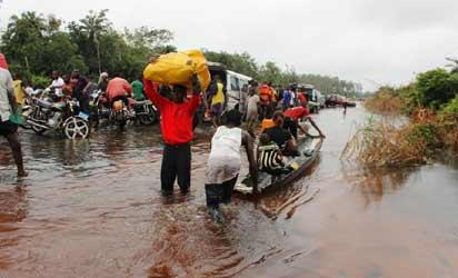 File photo: Travellers wading through East-West road cut-off  by flood as captured by Vanguard's Akpokona Omafuaire during a tour of the road by the South-South Regional Editor of Vanguard, Emma Amaize recently.