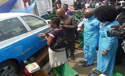 *Chairman of occasion, Mr. Tony Elumelu (2nd l) helping the first winner of a brand new car at the 2012 Word of Life Bible Church/Eagle Flight Micro-Finance Bank poverty alleviation programme, Mrs. Jennifer Tejiri Osatemu (left) to open the car while initiator and CAN president, Pastor Ayo Oritsejafor (2nd r) and wife, Pastor (Mrs.) Helen Oritsejafor (right) watch with keen interest.