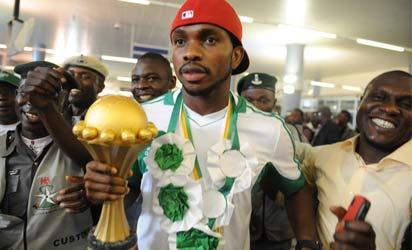 Skipper of Nigerian football team Joseph Yobo (C) holding the Africa Cup of Nations trophy arrives at the airport in Abuja, on February 12, 2013. The newly crowned African champions Nigerian Super Eagles arrives in Abuja to a warm reception by fans and government officials after defeating Burkina Faso to win the 2013 African Cup of Nations in South Africa. AFP PHOTO