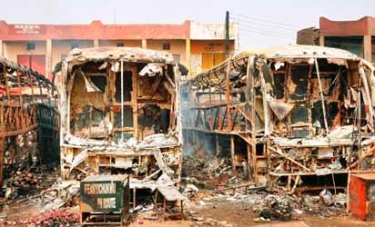 File: Burnt luxury buses lie in the parling area at New Road bus station in Sabon Gari district in northern Nigerian's largest city of Kano on March 19, 2013. Two suicide bombers rammed their car into a bus laden with passengers at the motor park, killing at least more than 22 people and injuring 65 others, and the  following explosion burnt five buses. AFP PHOTO