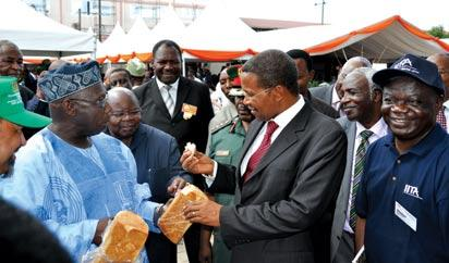 *African leaders share 40 percent cassava bread. The Goodwill Ambassador for the International Institute of Tropical Agriculture (IITA), former Nigeria's President Olusegun Obasanjo (left); former President of Tanzania, Benjamin Mkapa (next to Obasanjo from left); Tanzania's President, Dr Mrisho Jakaya Kikwete (dressed in red tie and holding cassava bread); and IITA Director for Eastern Africa, Dr Victor Manyong (far right); having a taste of the 40 percent cassava bread during the inauguration of IITA Science Building in Dar es Salaam