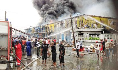 No fewer than 150 shops were razed, yesterday, at the Trinity Spare Parts Market in Ajegunle area of Lagos. Above: The raging fire and rescue operation at the scene.