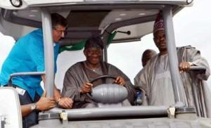 President Goodluck Jonathan (m) being assisted by Mr Hartlied Harald, Asphalt Supervisor, Julius Berger (left) and Gov Ibikunle Amosun of Ogun state, operating construction equipment during the flag off ceremony of Lagos Ibadan Expressway Reconstruction  in Sagamu  photo by Joe Akintola