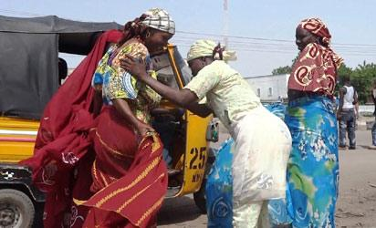 A female vigilante frisks two women passengers of a motorized rickshaw on July 19, 2013 in Maiduguri, where Boko Haram has carried out most of its deadly attacks.