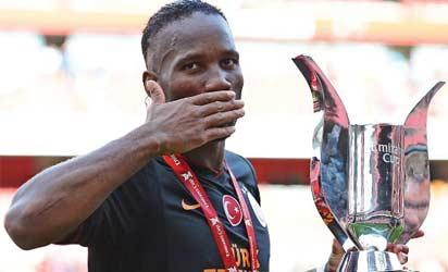 SWEET VICTORY: Drogba with the Emirates Cup Sunday. AFP.