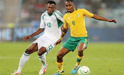 South Africa's Siphiwe Tsabalala is challenged by Nigeria's NNamdi Ouduamadi during a 2013 Nelson Mandela football Challenge friendly match between South Africa and Nigeria at Moses Mabhida Stadium on August 14, 2013 in Durban, South Africa. AFP PHOTO