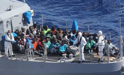 "In this image released by the US Navy, migrants are gathered on the deck of a Malta Armed Forced ship as they depart the amphibious transport dock ship USS San Antonio on October 17, 2013. The San Antonio rescued 128 men adrift from an inflatable raft that was threatening to capsize in rough seas in the Mediterraneanan on October 16 after responding to a call by the Maltese Government. ""AFP PHOTO"