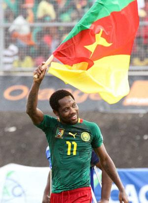 CAMEROON, Yaoundé : Cameroon's forward Jean Makoun waves a Cameroonian flag as he celebrates qualifying for the 2014 FIFA World Cup in Brazil after winning the second leg qualifying football match between Cameroon and Tunisia on November 17, 2013 in Yaounde. Cameroon won 4-1. AFP PHOTO