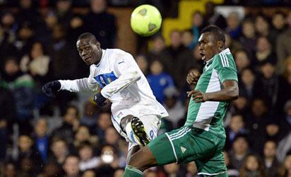 Mario Balotelli (L) vies with Nigeria's defender Azubuike Egwuekwe (R) during the International friendly