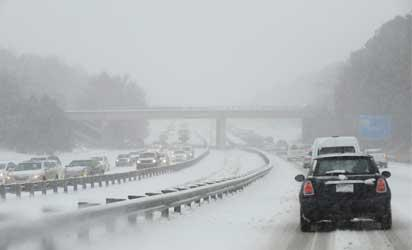 DURHAM, NC - FEBRUARY 12: Traffic on Durham Freeway 147 creeps along as compacted snow turns into ice on February 12, 2014 in Durham, North Carolina. Snow fell hard and fast in central North Carolina, resulting in abandoned cars and vehicular accidents by mid-afternoon.   Sara D. Davis/Getty Images)