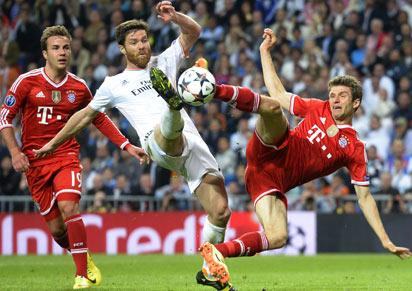 File: Real Madrid's midfielder Xabi Alonso (C) vies with Bayern Munich's midfielder Mario Goetze (L) and Bayern Munich's midfielder Thomas Mueller during the UEFA Champions League Semi Final in Madrid. It ended 1-0
