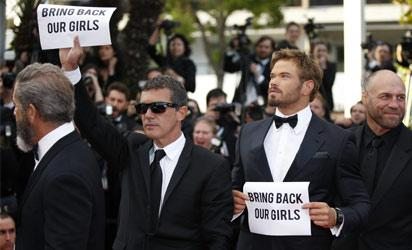 """FRANCE, Cannes : Members of the cast of """"The Expendables 3"""", Spanish actor Antonio Banderas (2ndL) and US actor Kellan Lutz (2ndR) hold cardboards reading """"# Bring back our girls"""", as a sign of support for the kidnapped Nigerian schoolgirls, while posing on the red carpet during the 67th edition of the Cannes Film Festival in Cannes, southern France, on May 18, 2014. AFP PHOTO /"""