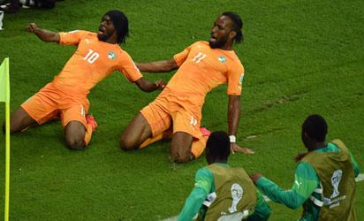 Gervinho of the Ivory Coast (L) celebrates scoring his team's second goal with teammate Didier Drogba during the 2014 FIFA World Cup Brazil Group C match between the Ivory Coast and Japan at Arena Pernambuco on June 14, 2014 in Recife, Brazil. (Photo FIFA)