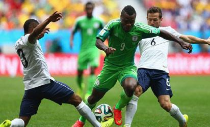 Nigeria's Emmanuel Emenike is challenged by France's Patrice Evra and Yohan Cabaye.