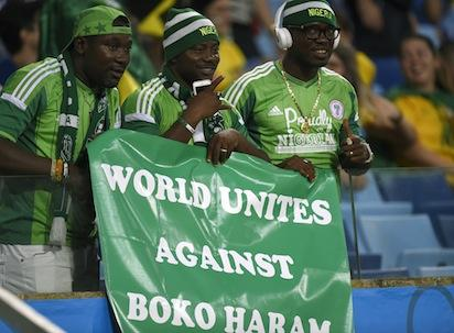 "Nigeria's fans hold a banner reading ""World Unites Against Boko Haram"" before the Group F football match between Nigeria and Bosnia-Hercegovina at the Pantanal Arena in Cuiaba during the 2014 FIFA World Cup on June 21, 2014. AFP PHOTO"