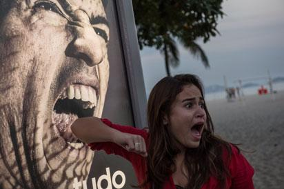 A tourist jokes in front of an advertisement with the portrait of Uruguay's forward Luis Suarez at Copacabana beach in Rio de Janeiro, Brazil, on June 26, 2014. Sportswear giant Adidas said Thursday it would stop using Luis Suarez, one of its key promotional stars, for World Cup adverts after his four-month ban from football activities for biting Italian Giorgio Chiellini. AFP PHOTO / YASUYOSHI CHIBA