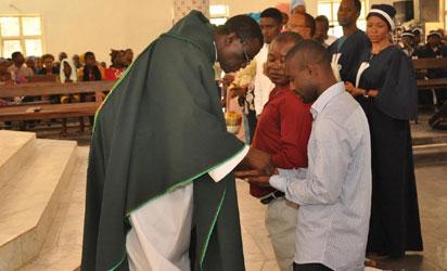 REV.FR. RAPH ASIKA  (L),PRESENTING HOLY COMMUNION ON PARISHIONERS HAND DUE TO FEAR OF EBOLA  SANITISER ON  THE HANDS OF ST PAUL CATHOLIC CHURCH GWAGWALADA ON SUNDAY (10/8/14)./NAN