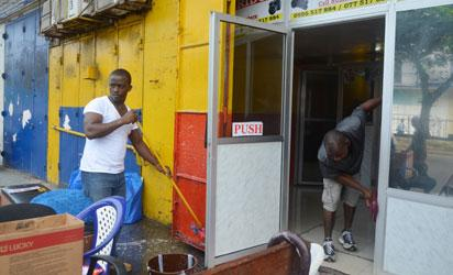 Men clean their shop in Monrovia where offices were closed for disinfection against the epidemic of the haemorrhagic fever Ebola on August 1, 2014. The head of the World Health Organization and presidents of the west African countries suffering the world's worst-ever Ebola outbreak meet in Guinea today to launch a $100 million (75 million euros) emergency joint response plan.   AFP PHOTO
