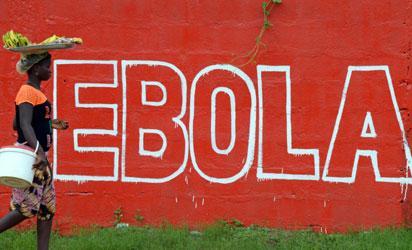 """File: A seller of bananas walks past a slogan painted on a wall reading """"Ebola"""" in Monrovia on August 31, 2014. Liberia on August 30, 2014 said it would deny permission for any crew to disembark from ships at the country's four seaports until the Ebola epidemic ravaging west Africa was under control. AFP PHOTO"""