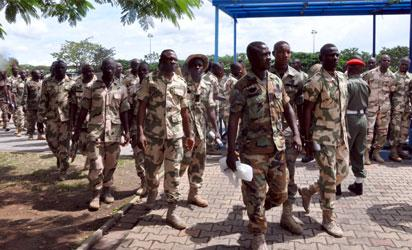 Soldiers tasked with fighting Boko Haram militants arrive to face trials for mutiny in Abuja on October 2, 2014. Nearly 100 soldiers tasked with fighting Boko Haram militants in Nigeria's far northeast appeared at a military court martial on Thursday, facing a range of charges including mutiny. The hearing comes just weeks after a tribunal sentenced 12 soldiers to death following their conviction for shooting at their commanding officer in the Borno state capital, Maiduguri, in May. AFP PHOTO