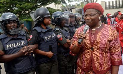 Leader of the #BringBackOurGirls campaign Oby Ezekwesili speaks as policewomen block supporters of the 219 Chibok schoolgirls kidnapped by Boko Haram militants from marching to the president's official residence in Abuja on October 14, 2014.  Nigerian police on Tuesday blocked supporters of 219 schoolgirls kidnapped by Boko Haram militants from marching on the president's official residence on the six-month anniversary of the abduction. A wall of female officers in full riot gear formed the first line of a barricade in front of less than 100 members of the Bring Back Our Girls campaign, preventing them from setting out.AFP PHOTO