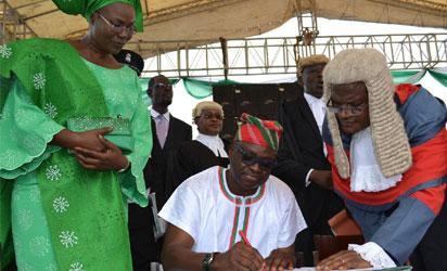 FAYOSE—Governor Ayo Fayose of Ekiti State (M), taking Oath of Office before the Chief Judge of Ekiti, Justice Ayodeji Daramola, in Ado-Ekiti, yesterday. With them is the governor's wife, Mrs Feyisetan Fayose. Photo: Dare Fasube.