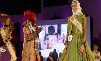 Winner of the 2014 World Muslimah Awards Fatma Ben Guefrache (R) of Tunis reacts next to runner up Nazreen Ali (L) of India and Miss Muslimah 2013 Obabiyi Aishah Ajibola (C) during the grand final in Yogyakarta on November 22, 2014. An eclectic mix of women from around the world competed in the final of a pageant exclusively for Muslims in Indonesia on November 21, seen as a riposte to Western beauty contests. The women, who include a doctor and computer scientist, are set to parade in glittering dresses against the backdrop of world-renowned ancient temples for the final in the world's most populous Muslim-majority country. AFP PHOTO