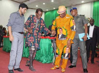 Anambra State governor , Chief Willie Obiano (2nd right), assisting one of the  beneficiaries, during the presentation of Prosthetic Limbs Fittings, on Tuesday.