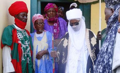 The emir of Kano, Muhammadu Sunusi II (C), visits the central mosque in northern Nigeria's largest city of Kano on November 29, 2014, a day after twin suicide blasts hit the mosque during weekly Friday prayers. At least 120 people were killed and 270 others wounded when two suicide bombers blew themselves up and gunmen opened fire during weekly prayers at the mosque, a week after the emir of Kano, Muhammad Sanusi II, of one of Nigeria's top Islamic leaders called on northerners to defend themselves against Boko Haram Islamists that have been carrying out deadly attacks and seizure of territory in the northeast. AFP PHOTO