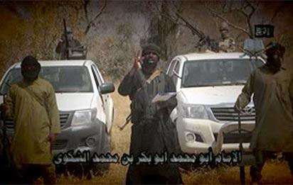 """In this screen grab image taken on February 9, 2015 from a video made available by Islamist group Boko Haram, leader Abubakar Shekau (C) makes a statement at an undisclosed location.  Boko Haram leader Abubakar Shekau vowed in a new video released on January 9, 2015 that the group would defeat a regional force fighting the militants in Nigeria's far northeast, Niger and Cameroon.""""AFP PHOTO / BOKO HARAM"""" -"""