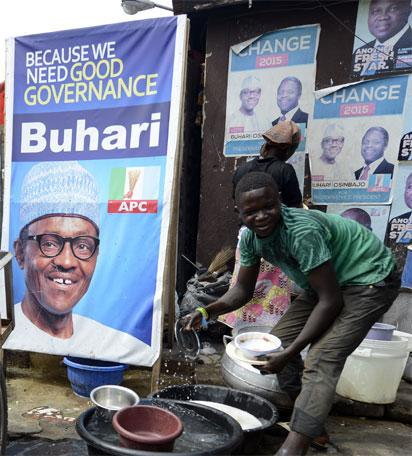 A roadside restaurant features on March 12, 2015 a poster of main opposition All Progressives Congress (APC) presidential candidate Mohammadu Buhari in Lagos. Buhari, the 72-year-old candidate of the APC is in neck-and-neck with President Goodluck Jonathan in the closely fought election campaign, which initially was expected to be held on February 14, but rescheduled for March 28 due to security concern. AFP PHOTO