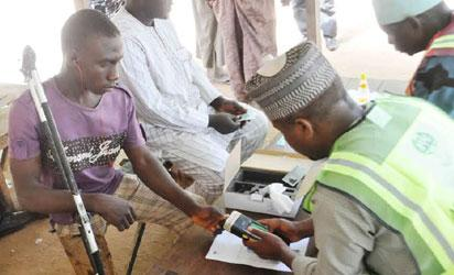 INEC OFFICIAL CHECKING THE THUMB OF A PHYSICALLY CHALLENGED VOTER, DURING THE TESTING OF SMART CARD READER AT HORARE WARD AND JOGEL POLLING UNIT IN JAMA,ARE LGA OF BAUCHI STATE ON SATURDAY.