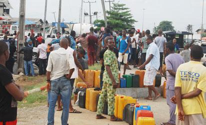 Long queue of jerry cans at a petrol station as fuel scarcity bites harder, yesterday. Photo: Joe Akintola, Photo Editor.