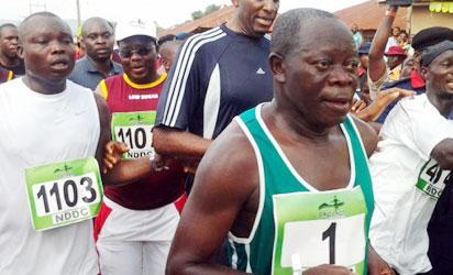 Governor Adams Oshiomhole (1) taking part in the Okpekpe Road Race