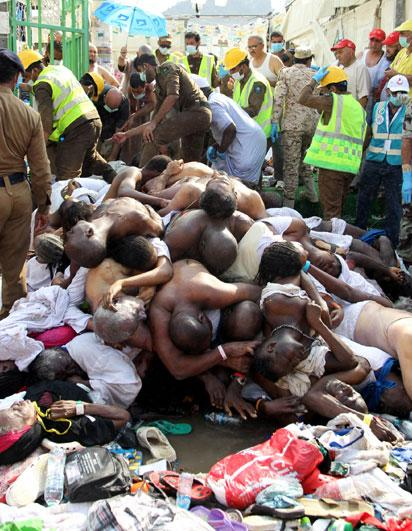 Saudi emergency personnel stand near bodies of Hajj pilgrims at the site where at least 717 were killed and hundreds wounded in a stampede in Mina, near the holy city of Mecca, at the annual hajj in Saudi Arabia on September 24, 2015. The stampede, the second deadly accident to strike the pilgrims this year, broke out during the symbolic stoning of the devil ritual, the Saudi civil defence service said. AFP PHOTO / STR