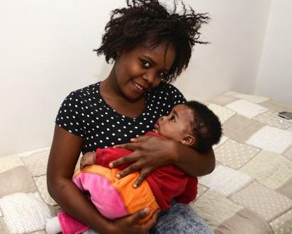 """Stephanie from Nigeria poses on October 1, 2015 with her daughter Francesca Marina, born on May 3, 2015 during a rescue operation of the Italian Navy off the coast of Sicily. Dubbed """"the princess of migrants"""", a Nigerian baby born on the Italian ship that rescued her mother in the Mediterranean has become a symbol of hope for those braving the perilous crossing in search of a new life. In early May, when the international press was cooing over the birth of Princess Charlotte into the British royal family, the photograph of another baby also landed in the headlines. Tiny Francesca Marina was shown sleeping, nestled in pink gauze, a closed fist resting against her face. AFP"""