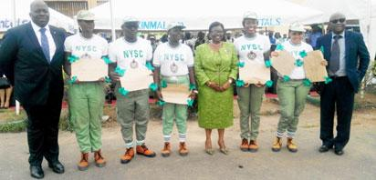 AWARDS: From left, Mr. Ola Olabinjo, Executive Director, Heritage Bank, Dr. Ibironke Shodipe, Permanent Secretary, Inter-Governmental Relations (middle), NYSC, Lagos State Coordinator, Mr. Cyril Akhanemhe and 2014 Batch 'C'' five outstanding corps members during passing out parade held at its Ipaja camp.