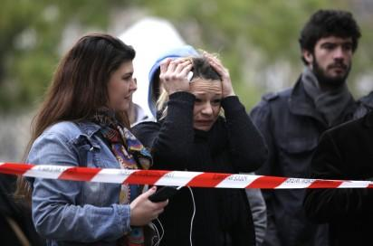 A woman reacts as she looks at the flowers and messages left at a rail cordon close to the Bataclan theatre in the 11th district of Paris on November 14, 2015, the day after a series of attack on the city resulting in the deaths of more than 128 individuals. Some 80 people were gunned down at the Bataclan theatre in Paris late November 13, during a concert by the US band Eagles of Death Metal. AFP PHOTO / KENZO TRIBOUILLARD