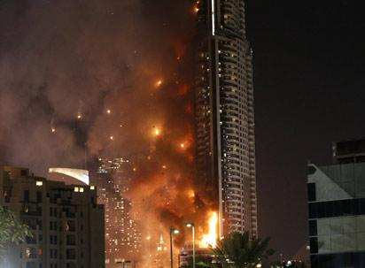 Flames rip through the Address Downtown hotel after it was hit by a massive fire, near the world's tallest tower, Burj Khalifa, in Dubai, on December 31, 2015. People were gathering to watch New Year's Eve celebrations when the hotel caught on fire, with the cause of the blaze still unknown according to the emirate's police chief. AFP PHOTO / KARIM SAHIB / AFP / KARIM SAHIB