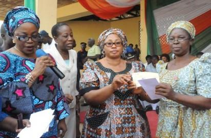 Commissioner for Women Affairs & Social Development, Mrs. Olasinmi Akindele-Odunmbaku (2nd right), presenting a cheque to one of the widows of the fallen heroes, Dr.(Mrs) Taiwo Agoyi (right), while the Chairman, Micro Credit Agency, Mrs Banke Sutton (left), watches