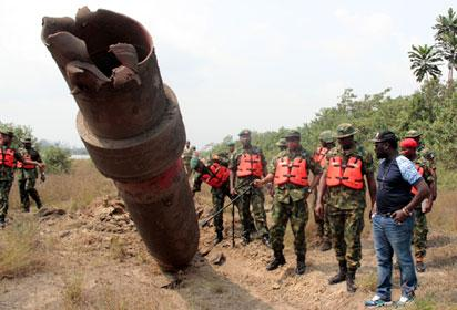 BOMBED—Major Gen. Alani Okunola, Commander of the Joint Task Force (Middle); pointing to part of a severed pipeline, while Brig. Gen. Farouk Yahaya, Commander, 4 Brigade, Benin (2nd left); Lt. Col. Igwe P. Omoke, Commanding Officer, 3 Battalion Effurun (2nd right)and others watch during inspection of the gas pipeline in Warri South-West Local Government Area of Delta State bombed by suspected militants. Inset: Other damaged areas. Photos: Akpokona Omafuaire.