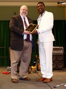 Fred D. Baldini, Ph.D. Dean, College of Health & Human Services, giving the award to the rep. of Dr. Jonathan, Reno Omokri
