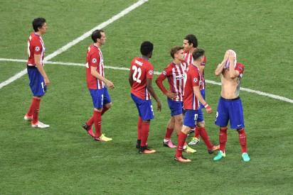 Atletico Madrid players walk off the pitch after loosing to Real Madrid in the UEFA Champions League final football match at the San Siro Stadium in Milan, on May 28, 2016.  Real Madrid beat city rivals Atletico for the second time in three years to win the Champions League for the 11th time. / AFP PHOTO / TIZIANA FABI