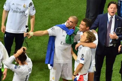 From left: Real Madrid's Portuguese defender Pepe, Portuguese forward Cristiano Ronaldo and Real Madrid's Croatian midfielder Luka Modric celebrate after Real Madrid won the UEFA Champions League final football match over Atletico Madrid at San Siro Stadium in Milan, on May 28, 2016.  Real Madrid beat city rivals Atletico for the second time in three years to win the Champions League for the 11th time. / AFP PHOTO / GIUSEPPE CACACE