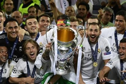 Real Madrid's Spanish defender Sergio Ramos (C) lifts the trophy next to Real Madrid's Croatian midfielder Luka Modric (L) and Real Madrid's French forward Karim Benzema (R) after Real Madrid won the UEFA Champions League final football match between Real Madrid and Atletico Madrid at San Siro Stadium in Milan, on May 28, 2016. / AFP PHOTO / PIERRE-PHILIPPE MARCOU