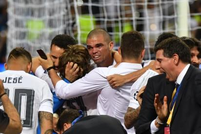 Real Madrid's Portuguese defender Pepe (C) celebrates with teammates after Real Madrid won the UEFA Champions League final football match over Atletico Madrid at San Siro Stadium in Milan, on May 28, 2016. / AFP PHOTO / GERARD JULIEN