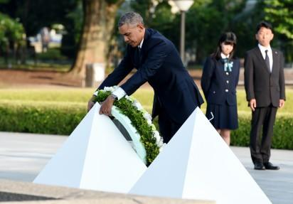 """US President Barack Obama places a wreath at the cenotaph in the Peace Momorial park in Hiroshima on May 27, 2016 with Japanese Prime Minister Shinzo Abe. Obama on May 27 paid a moving tribute to victims of the world's first nuclear attack. / AFP PHOTO / TOSHIFUMI KITAMURA / """"The erroneous mention[s] appearing in the metadata of this photo by TOSHIFUMI KITAMURA has been modified in AFP systems in the following manner: [removing reference to POOL] instead of [POOL]. Please immediately remove the erroneous mention[s] from all your online services and delete it (them) from your servers. If you have been authorized by AFP to distribute it (them) to third parties, please ensure that the same actions are carried out by them. Failure to promptly comply with these instructions will entail liability on your part for any continued or post notification usage. Therefore we thank you very much for all your attention and prompt action. We are sorry for the inconvenience this notification may cause and remain at your disposal for any further information you may require."""""""